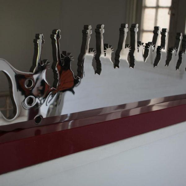 The Merger. Trabajando por la libertad. 2011. Acero inoxidable calado sobre base de cuarzo. 35 x 129 x 12.7 cm.