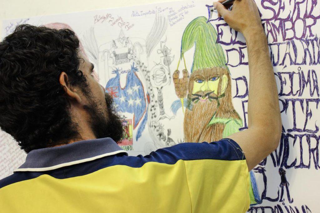 Josvedy Jove Junco, artista de Art Brut Project Cuba, realiza uno de sus dibujos de gran formato en una de las salas de RIERA STUDIO, La Habana, 2014. Foto: Derbis Campos. Archivos de la Colección Art Brut Project Cuba, La Habana.