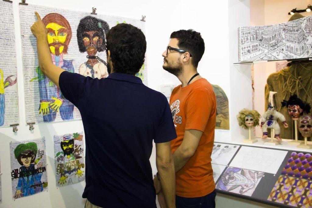 Josvedy Jove Junco (a la izquierda y de espaldas), artista de Art Brut Project Cuba, muestra sus obras a un visitante durante la inauguración de la exhibición Primera Exhibición de la Colección de Art Brut Project Cuba, RIERA STUDIO, La Habana, 2016. Foto: Derbis Campos. Archivos de la Colección Art Brut Project Cuba, La Habana.