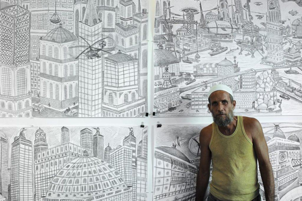 Damián Valdés Dilla, artista de Art Brut Project Cuba, delante de un panel de sus obras de la colección Art Brut Project Cuba, RIERA STUDIO, La Habana, 2014. Foto: Derbis Campos. Archivos de la Colección Art Brut Project Cuba, La Habana.