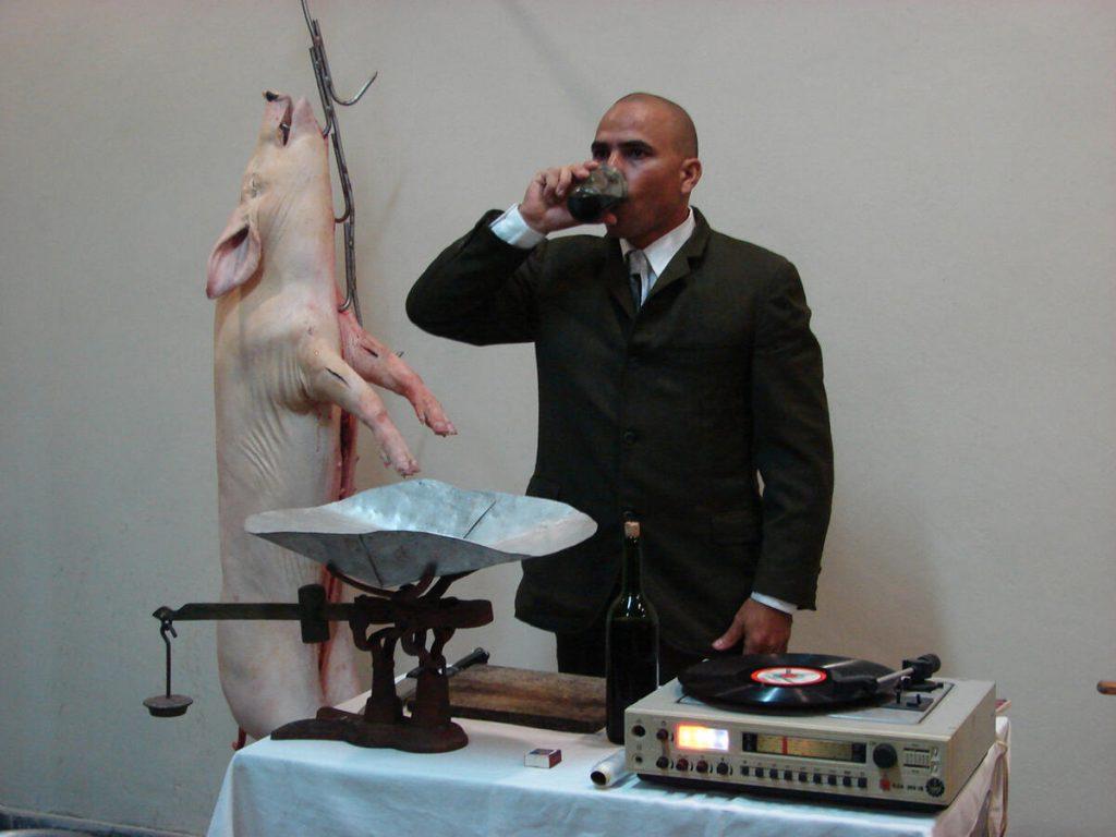 """Del performance de Mayimbe o Mayim-B (José Miguel Díaz), tesela de peso en/para la muestra colectiva Escrituras Profanas, de 2008. El artista (d)escribiría a modo de correlato, en el catálogo previsto, lo siguiente: """"La acción, cuenta con un cerdo de [100 libras que cuelga] de la pared por un gancho de carnicería. Una mesa con (…) cuchillo, pesa, una botella de vino tinto de producción nacional, un vaso, un paño blanco, una hornilla con carbón natural (…) y un marcador de metal con el texto en relieve: 'Socialismo'. Vestido con traje de gala, accedo al cerdo (…) retirando la carne de los huesos, así como la manteca de la carne. Mientras, escucho a través de un tocadiscos ruso (…) la reproducción [de un] discurso que el Líder Fidel Castro pronunciara en la década del 60 (…) Durante 2 horas aproximadamente ofreceré al público porciones iguales (…) después de haber marcado sobre cada ración el texto [Socialismo] al rojo vivo"""". (Foto: archivo de CTPPO, 1998-2011)."""
